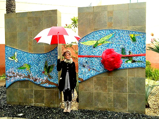 Katherin England with Umbrella in front of Mosaic Public work